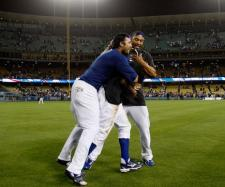 Andre Ethier and Matt Kemp sandwich Rafael Furcal and pour champagne on him.JPG